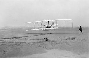 Il Flyer si solleva per il suo primo, storico volo il mattino del 17 dicembre 1903. Orville è ai comandi e Wilbur lo osserva da vicino. La fotografia, una delle più riprodotte del Novecento, è stata scattata da John Daniels.