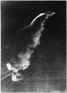 Foto aerea giapponese dell'attacco iniziale sulla Prince of Wales (in alto) e la Repulse (in basso). Un largo e denso pennacchio di fumo viene emesso dalla Repulse, che è stata appena colpita da una bomba. La Prince of Wales emette un denso fumo a riprova del tentativo di aumentare la sua velocità