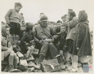 Un soldato americano divide i suoi rifornimenti natalizi con i bambini di San Benedetto Val di Sambro, 11 dicembre 1944.